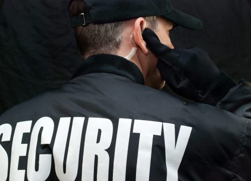 Close-up of a security guard listening to his earpiece. Back of jacket showing.